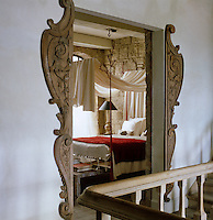 Wooden carvings adapted from an antique French pharmacy cabinet frame the door to the master bedroom