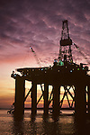 Oil drilling rig in Elliot Bay at sunset moored at the Port of Seattle for repairs, Seattle, Washington State USA.