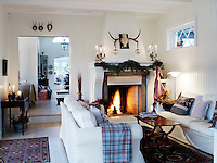 A fire blazes in the hearth of the cosy living room, furnished with comfortable sofas and homely cushions