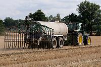 GERMANY, farming, tractor with slury wagon on field / DEUTSCHLAND, Mecklenburg Vorpommern, Traktor mit Guellewagen bringt Guelle auf ein Stoppelfeld aus, zu viele Nitrate belasten das Grundwasser