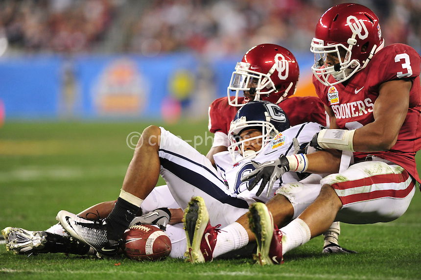 Jan 1, 2011; Glendale, AZ, USA; Oklahoma Sooners defensive backs Jonathan Nelson (3) and Demontre Hurst (19) separate Connecticut Huskies wide receiver Kashif Moore (82) from the ball in the 4th quarter of the 2011 Fiesta Bowl at University of Phoenix Stadium.  The Sooners won the game 48-20.