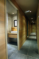 This narrow wood-clad corridor has a floor of slate tiles