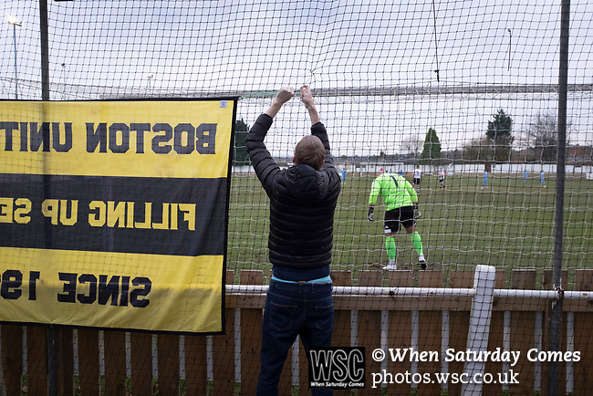 Atherton Collieries 1, Boston United 0, 23/11/19. Alder House, FA Trophy, third qualifying round. A visiting supporter tying a flag to fencing before Atherton Collieries played Boston United in the FA Trophy third qualifying round at the Skuna Stadium. The home club were formed in 1916 and having secured three promotions in five season played in the Northern Premier League premier division. This was the furthest they had progressed in the FA Trophy and defeated their rivals from the National League North by 1-0, Mike Brewster scoring a late winner watched by a crowd of 303 spectators. Photo by Colin McPherson.