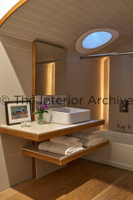 Modern bathroom with arched tiled ceiling and porthole skylight