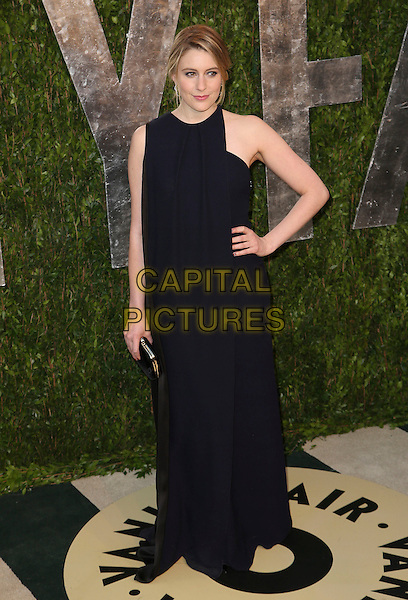 Greta Gerwig.2013 Vanity Fair Oscar Party following the 85th Academy Awards held at the Sunset Tower Hotel, West Hollywood, California, USA..February 24th, 2013.oscars full length dress black sleeveless dress hand on hip navy blue clutch bag.CAP/ADM/SLP/DOW.©Dowling/StarlitePics/AdMedia/Capital Pictures