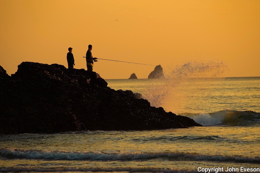 Father and son fishing from a rock at sunset, Perranporth, Cornwall.