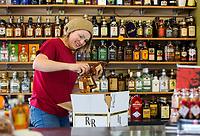 NWA Democrat-Gazette/JASON IVESTER<br /> Ivy Hamilton stocks liquor bottles Monday, March 13, 2017, at Lefty's Liquor in Rogers.