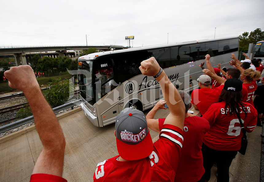 Ohio State Buckeye fans cheer as the team buses head to a loading dock under the stadium before the college football game between the Ohio State Buckeyes and the Navy Midshipmen at M&T Bank Stadium in Baltimore, Saturday morning, August 30, 2014. (The Columbus Dispatch / Eamon Queeney)