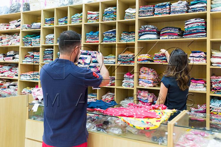 Vendedora em loja de roupas infantis atendendo cliente, São Paulo - SP, 10/2017