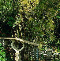 A concrete balustrade and random sculptures are seen here against a backdrop of bamboo