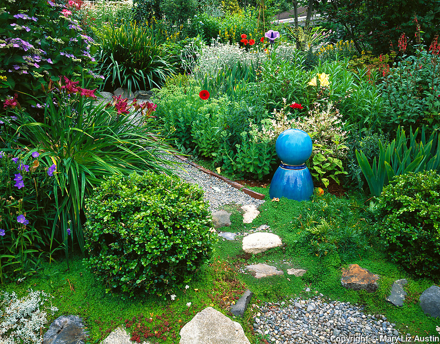 Vashon Island, WA<br /> Gravel pathway leads past a blue gazing ball into a garden of summer perennials in a cottage garden
