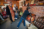 A young boy adds a yule log to the fire as Rev. Stephen Tumbas watches during the traditional burning of the yule longs (badnjak) after the Christmas Eve Vigil Service, St. Sava Serbian Orthodox Church, Jackson, Calif.
