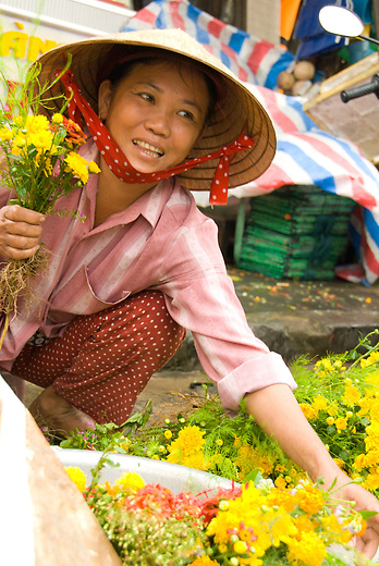 A woman in the markets of Hoi An selling flowers.