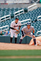 Birmingham Barons first baseman Nick Basto (20) holds on Brian O'Grady (21) during a game against the Pensacola Blue Wahoos on May 9, 2018 at Regions FIeld in Birmingham, Alabama.  Birmingham defeated Pensacola 16-3.  (Mike Janes/Four Seam Images)