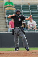 Home plate umpire Derek Gonzales calls a batter out on strikes during the South Atlantic League game between the West Virginia Power and the Kannapolis Intimidators at CMC-Northeast Stadium on May 1, 2014 in Kannapolis, North Carolina.  The Power defeated the Intimidators 5-4.  (Brian Westerholt/Four Seam Images)