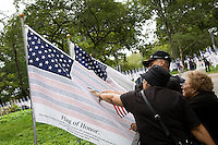 People look at one of three thousand flags displaying the names of the victims of the September 11th attacks in Battery Park in New York City, New York on the 10th anniversary of the September 11th attacks on 11 September 2011 in an effort to provide all New Yorkers who lived through the events of 9/11 a public place to gather and pay respects to those who were killed that day.