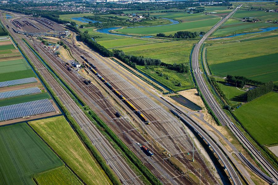 Nederland, Zuid-Holland, Zwijndrecht, 12-06-2009; Kijfhoek, rangeerterrein voor goederentreinen met overzicht van de opstelsporen, met afbuigend naar rechts de HSL. .De Betuweroute, die begint als Havenspoorlijn op de Maasvlakte, verbindt via Kijfhoek de Rotterdamse haven met het achterland. Kijkhoek huisvest Keyrail, exploitant Betuweroute en is in beheer bij ProRail.Het rangeeremplacement dient voor het sorteren van goederenwagons waarbij gebruik gemaakt wordt van de zwaartekracht, het heuvelen: de wagons worden de heuvel opgeduwd, bij het de heuvel afrollen komen ze, door middel van wissels, op verschillende verdeelsporen, railremmen zorgen voor het automatisch remmen van de wagons. Na het heuvelproces staan de nieuw samengestelde treinen op aparte opstelsporen.Kijfhoek, railway yard used by ProRail and Keyrail (Betuweroute operator). Kijfhoek connects via the Betuweroute (beginning as Havenspoorlijn on the Maasvlakte), through the port of Rotterdam with the hinterland. The shunting yard for sorting wagons makes use of gravity. The new trains are assembled on separate tracks.luchtfoto (toeslag), aerial photo (additional fee required).foto/photo Siebe Swart