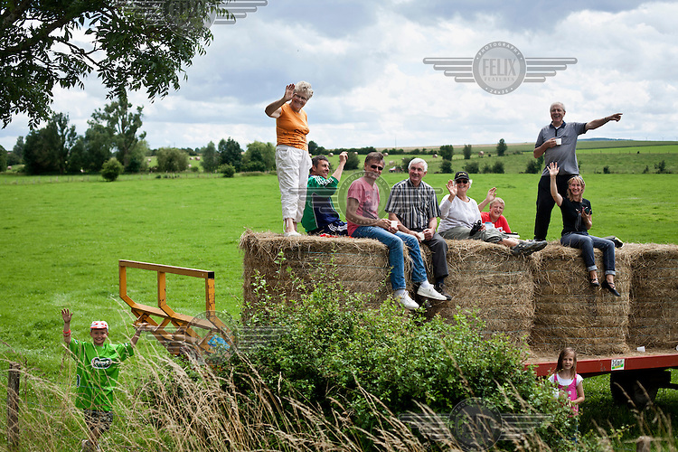 Local people sit on bails of hey in a field as they wait see the Tour de France cycling competition pass through their village.