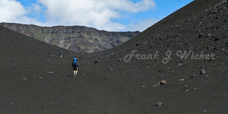 Two male hikers struggling up the black lava sand slopes of the crater in HALEAKALA NATIONAL PARK on Maui in Hawaii USA