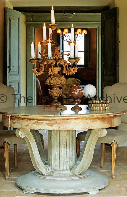 A large ornate candelabra sits on a Directoire restored table