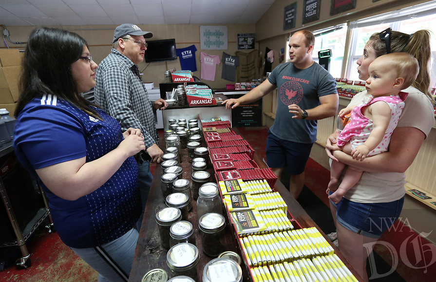 NWA Democrat-Gazette/DAVID GOTTSCHALK Jennifer Pocasangre (from left), manager of inventory and retail, and Rick Boosey, owner and founder of Kyya Chocolate, visit Wednesday, July 3, 2019, with CJ and Haley Cottey and their daughter Della, 2, Wednesday, July 3, 2019, at the Kyya Chocolate Factory and Tasting Room in Elm Springs. Kyya was the first bean to bar chocolate comparing in Arkansas and the name comes from the Greek, KAIA, which means pure, simple, or straight forward.
