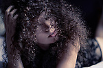 Artistic sensual portrait of a young woman lying on a bed looking at camera with her face partially covered with long curly hair