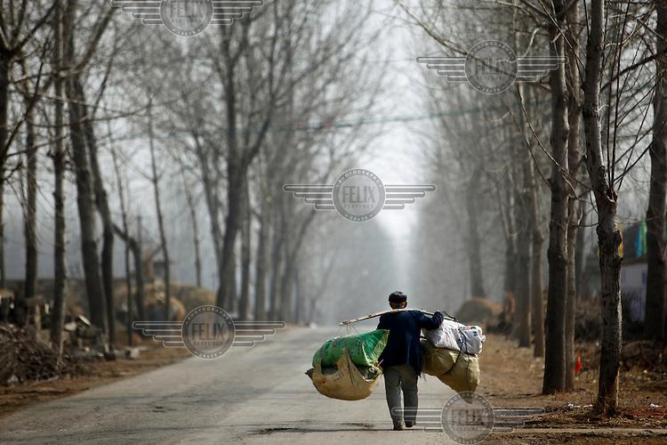 A man walks along a road carrying farm produce on a bamboo yoke balanced over his shoulder.