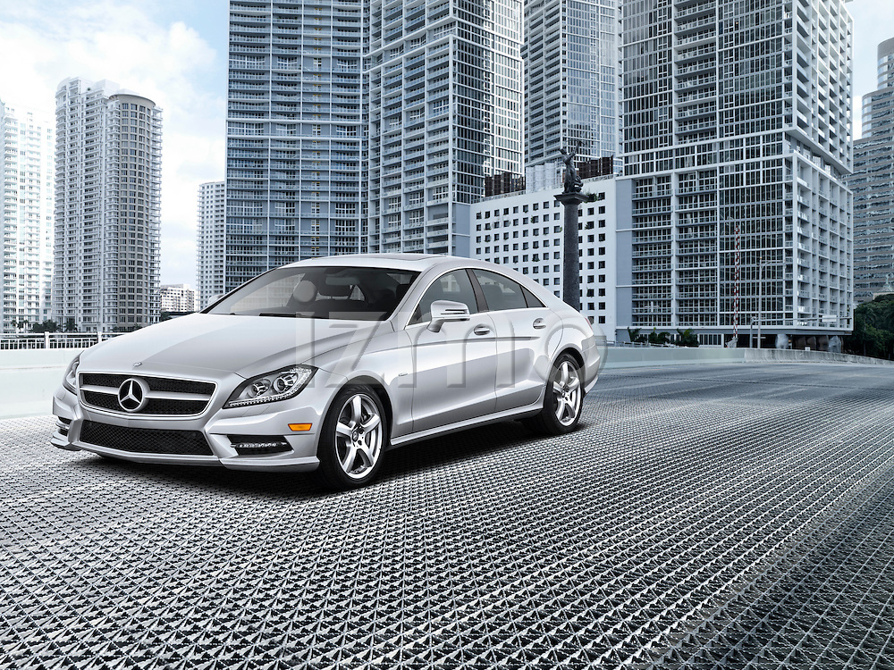 One silver 2012 Mercedes-Benz CLS Class Sedan outdoors on a bridge with cityscape in background.