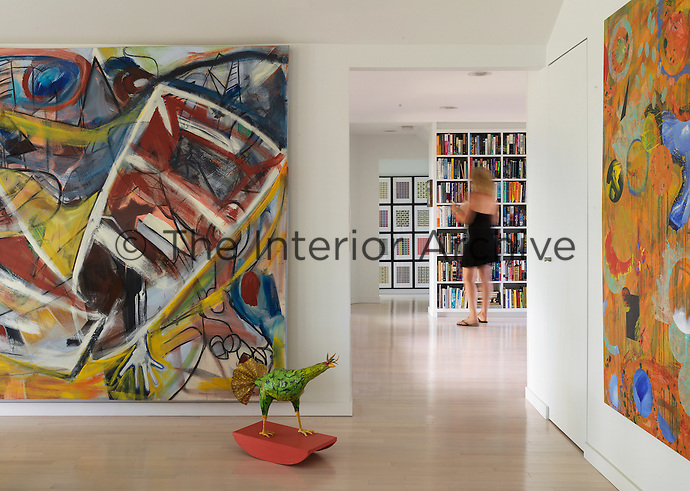 View from the living area with large abstract paintings towards the library where owner Shelley Weintraub stands looking at a book