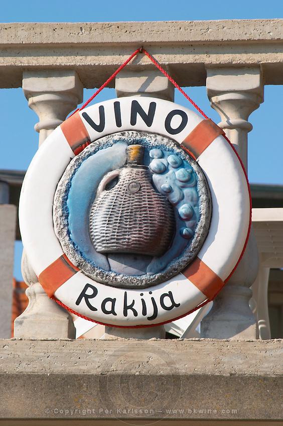 Sign looking like a life buoy advertising Vino wine and Rakija grappa type spirit with a jug of wine and grapes, hanging from a balustrade. Prizba village. Korcula Island. Prizba, Riva Apartments, Danny Franulovic. Korcula Island. Dalmatian Coast, Croatia, Europe.