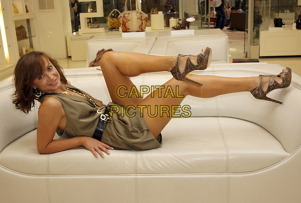KARINA SMIRNOFF.Visits Carmen Steffens held at The Carmen Steffens Store, Sherman Oaks, CA, USA, 4th June 2010..full length green khaki dress gold necklace sitting down  waist  belt black playsuit sandals lying down couch brown  shoes anklet .CAP/ADM/KB.©Kevan Brooks/AdMedia/Capital Pictures.