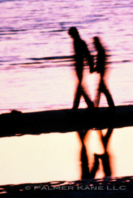 Blurred silhouette Couple Walking On Beach At dusk