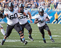 North Carolina offensive linemen Russell Bodine (60) and Lucas Crowley (65) block for running back TJ Logan (8). The North Carolina Tar Heels defeated the Pitt Panthers 34-27 at Heinz Field, Pittsburgh Pennsylvania on November 16, 2013.