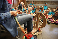 NWA Democrat-Gazette/DAVID GOTTSCHALK  The hands of Linda Christy are visible as she spins Wednesday, May 10, 2017, in front of a first grade class from Prairie Grove Elementary School in the Latta Barn at Prairie Grove Battlefield State Park. The state park hosted a Sheep to Shawl event for five first grade classes from the school that featured the spinning demonstration, sheep shearing, wool washing and a weaving demonstration.