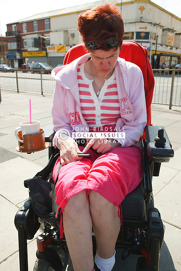 Wheelchair user with cerebral palsy using mobile phone.