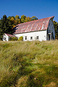 Barn with red roof at the Daniel Webster Birthplace site during the autumn months in Franklin, New Hampshire USA which is part of scenic New England..
