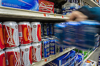 A shopper grabs cans of Budweiser  beer by the brewer Anheuser-Busch inBev in a supermarket in New York on Monday, February 25, 2013.  (© Richard B. Levine)