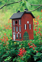 Painted faux brick townhouse birdhouse in red flowers of garden,