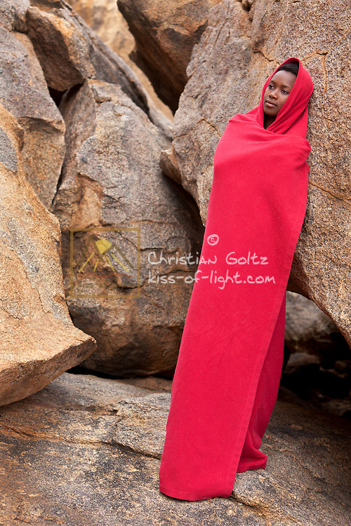 Black lady wrapped in red blanket standing near granite boulders