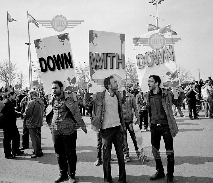 During celebrations marking the 35th anniversary of the Iranian Revolution a group of men hold placards that together read: 'DOWN WITH DOWN'. The complete slogan should be: 'DOWN WITH THE USA DOWN WITH ISRAEL' but their colleagues are missing.