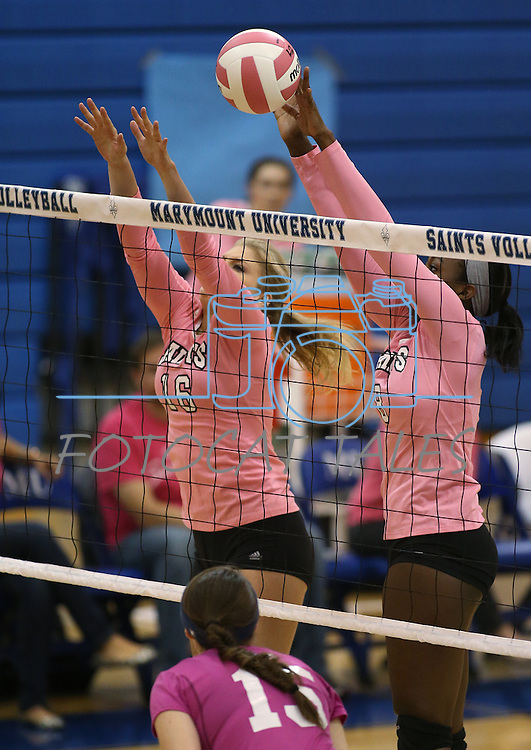 Marymount's Morgan McAlpin gets a block during a college volleyball match against Shenandoah at Marymount University in Arlington, Vir., on Tuesday, Oct. 8, 2013.<br /> Photo by Cathleen Allison