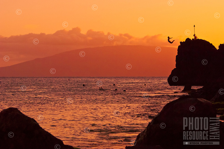 Sunset cliff diving off of Black Rock at Ka'anapali Beach, Maui