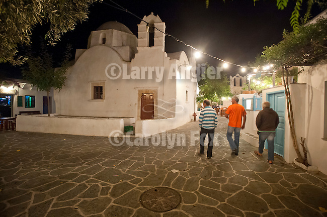 Three men strolling by the church at nighttime in the village squares of Chora, Folegandros, Cyclades, Greece