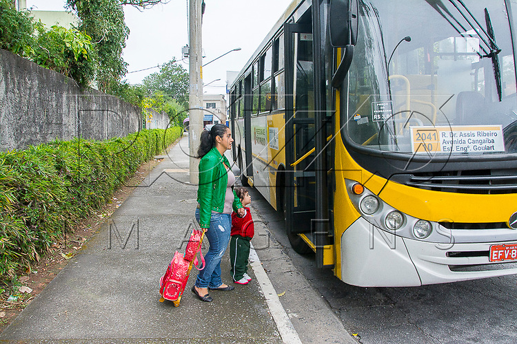 Mãe embarcando em um ônibus com a filha vestida com uniforme escolar, São Paulo - SP, 08/2016. Uso de imagem autorizado