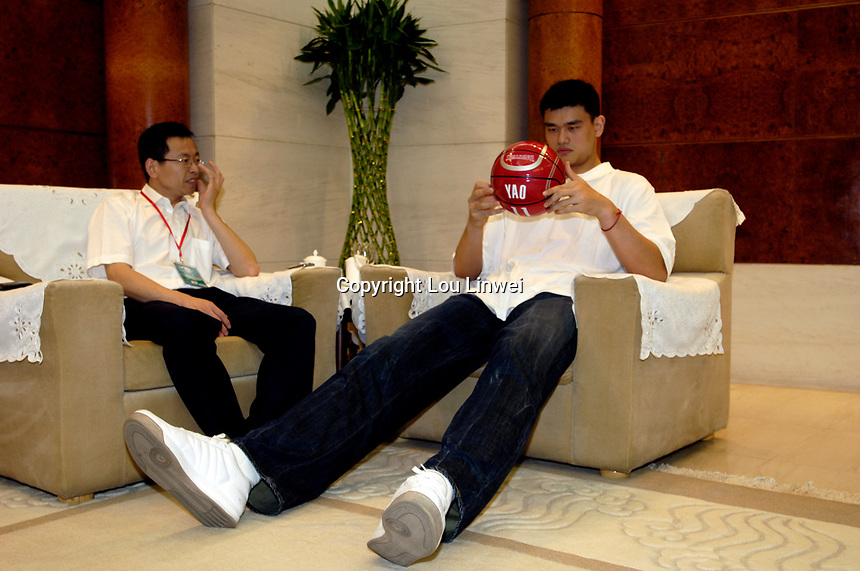 NBA Houston Rockets player Yao Ming plays with a basketball before a press conference for the 2007 Special Olympics while a man plays with a basketball in Beijing, China.  July 21, 2006. (photo by Lou Linwei/Sinopix)