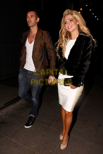 Tommy Williams & Nicola McLean.Hybrid and OK! Magazine London Fashion Week Party, Jewel Bar, London, England..22nd February 2012.full length white dress black jacket brown top jeans denim holding hands.CAP/AH.©Adam Houghton/Capital Pictures.