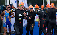 26 AUG 2012 - STOCKHOLM, SWE - Will Clarke (GBR) of Great Britain (second from left) runs to the swim after tagging team mate Vicky Holland (GBR) during the 2012 ITU Mixed Relay Triathlon World Championships in Gamla Stan, Stockholm, Sweden .(PHOTO (C) 2012 NIGEL FARROW)