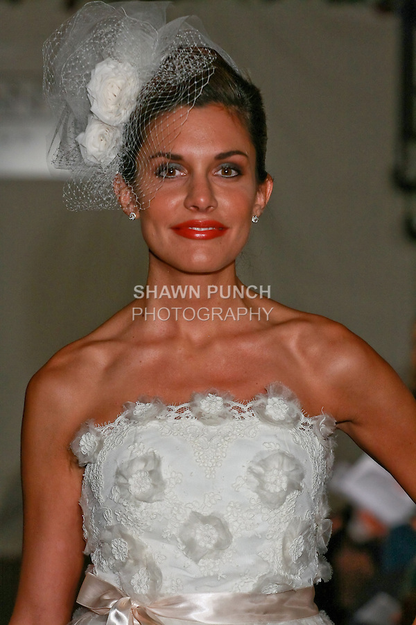 Model walks the runway in an Adriana wedding dress - silk organza rosettes and lace - by Sarah Jassir for the SARANTINA by Sarah Jassir Spring 2011 runway show, during New York Bridal Week Spring 2011.