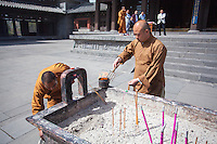 Buddhist monks tending to burning incense in front of a temple at the Yungang Grottoes in Datong, China