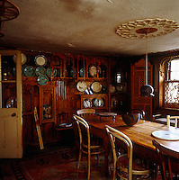 A collection of plates is displayed on the fretwork shelving in the dining room